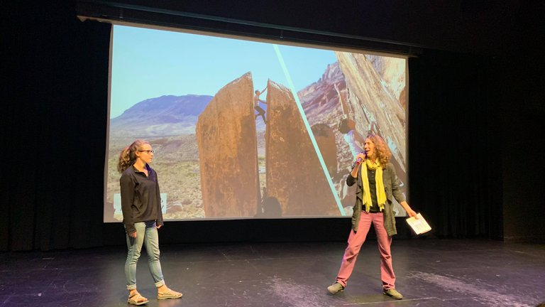 Shaelyn Silverman and Juliet Ryan-Davis MC ReelRock 14, in front of a slideshow showing people bouldering in a crack in boulder in Bishop CA.