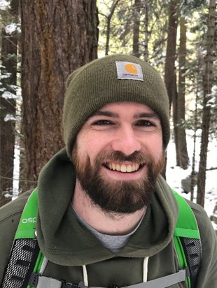 Photo of Benjamin Herren in a snow-covered forest with hiking gear.