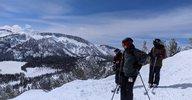 Two people on a snowy hillside look sideways toward the camera.