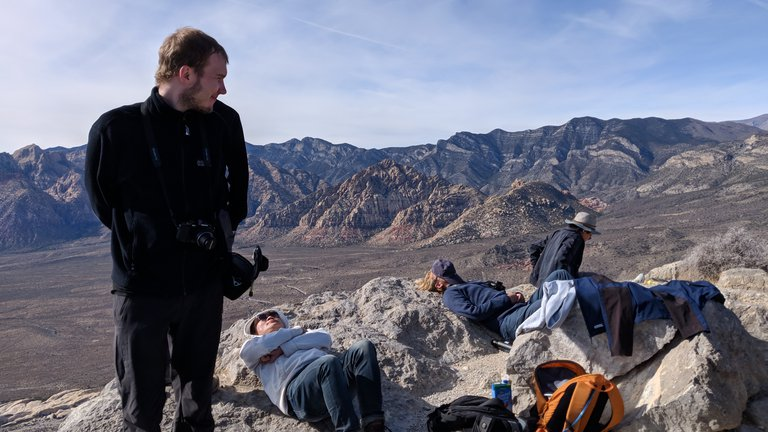A member of the Caltech Alpine Club, wearing a camera around his neck, stands in the foregrounds, twisting his head to look back behind him at a group of people sleeping on the ground on the peak of a mountain. Some have hats covering their faces. It is the middle of the day.