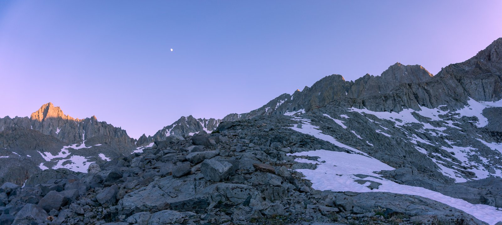 Photo of the high Sierra crest peaks with the moon above, and a little bit of remaining alpenglow on the highest peak and a patchy snow apron at dusk.