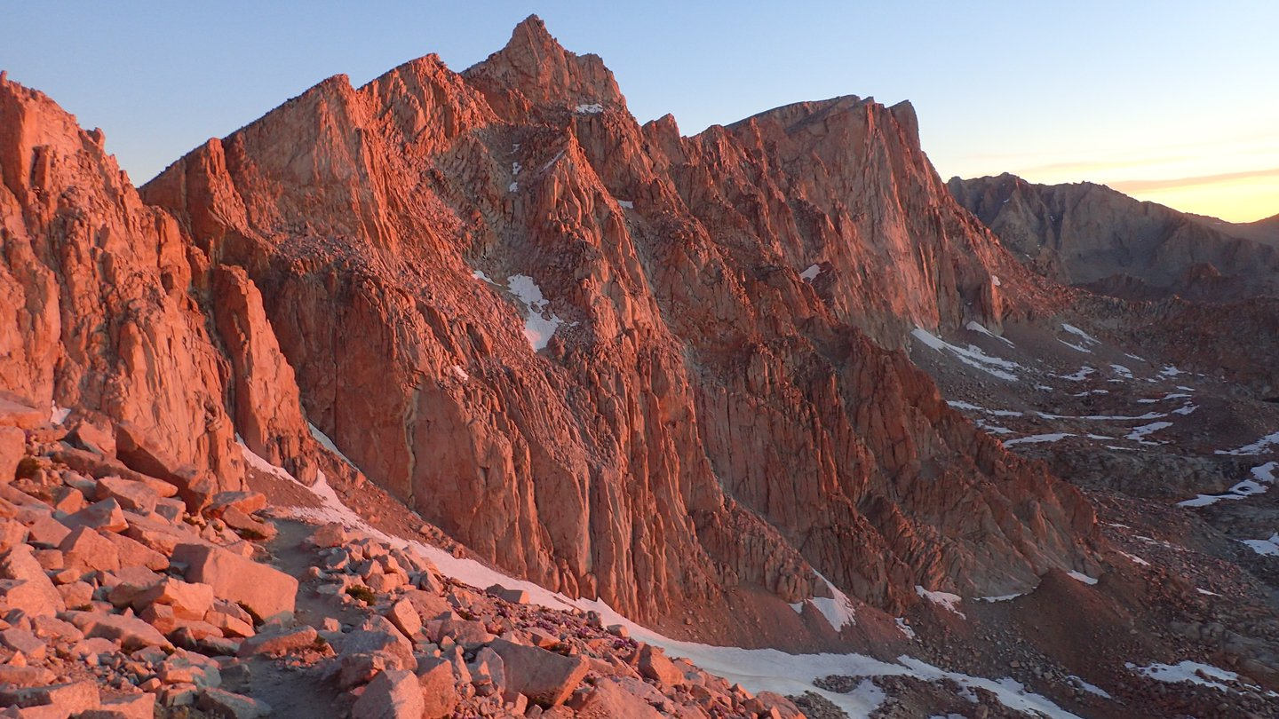 Rocky peaks in pink sunrise light. Mount Whitney is in the background