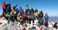 A large group of people from the Caltech Alpine Club posing among rocks at the summit of San Gorgonio mountain. A clear blue sky stretches out in the background, and the group stands on a slight slant, sloping left to right.