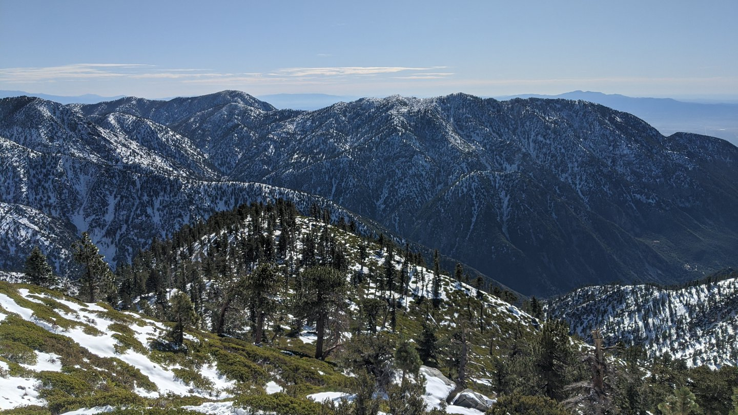 View down the valley from the hike on Mt Baldy. The ground is still half-covered in snow, and scarce treeds cover the hillsides. Blue skies.