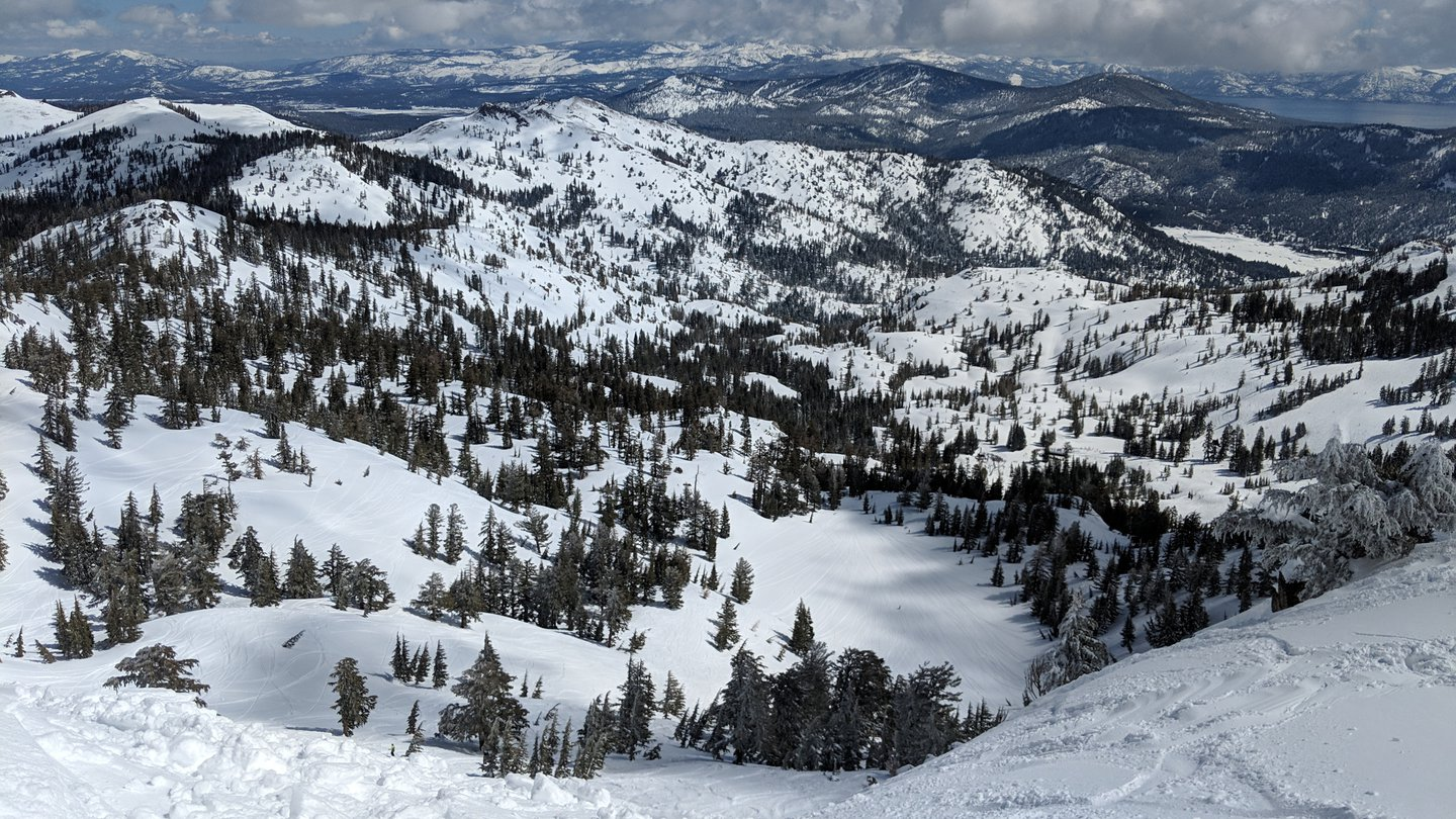 Sample view of the Squaw Valley Snow Resort in Lake Tahoe. Sidecountry slopes are in the foreground, and the background features a stretch of Lake Tahoe as well as Sierra Nevada mountains.