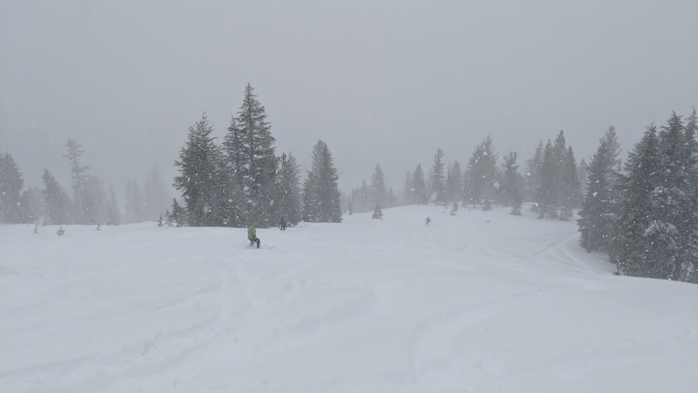 The beginning of February 2019 featured a 2 meter snow dump in one weekend. A few people are skiing in very deep snow, and the visibility is bad because of ongoing snowfall.