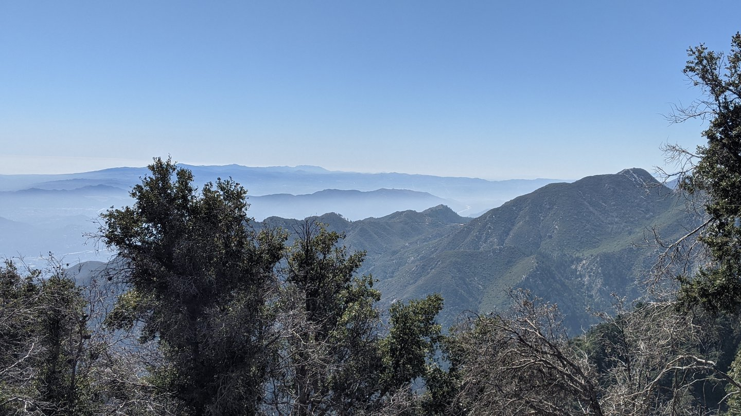 View over many rows of mountain tops, with low-lying haze in between. The mountains are covered in green vegetation.