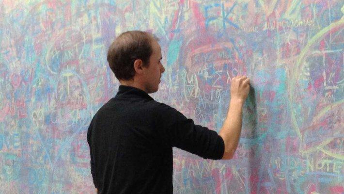 David Simons-Duffins writing on chalkboard
