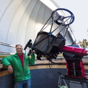 man in green jacket stands next to a telescope pointed at the sky
