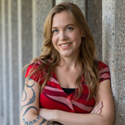 woman with strawberry blonde hair, red shirt, and tattoos leans again a wall
