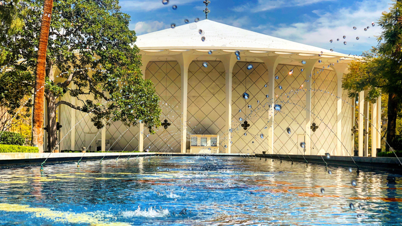 """a view of the Beckman auditorium with the """"gene pool"""" fountain in the foreground"""
