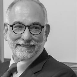 b&w photo of a bald man with white beard wearing glasses