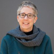 woman with closely cropped grey hair, glasses, and teal shirt