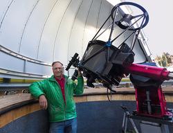 man in green jacket standing new telescope