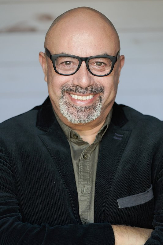 Herbert Sigüenza with glasses, a headshot photo.