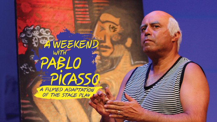 an older man with white hair and wearing a black and white striped tank top stands in front of some art in the style of Pablo Picasso.