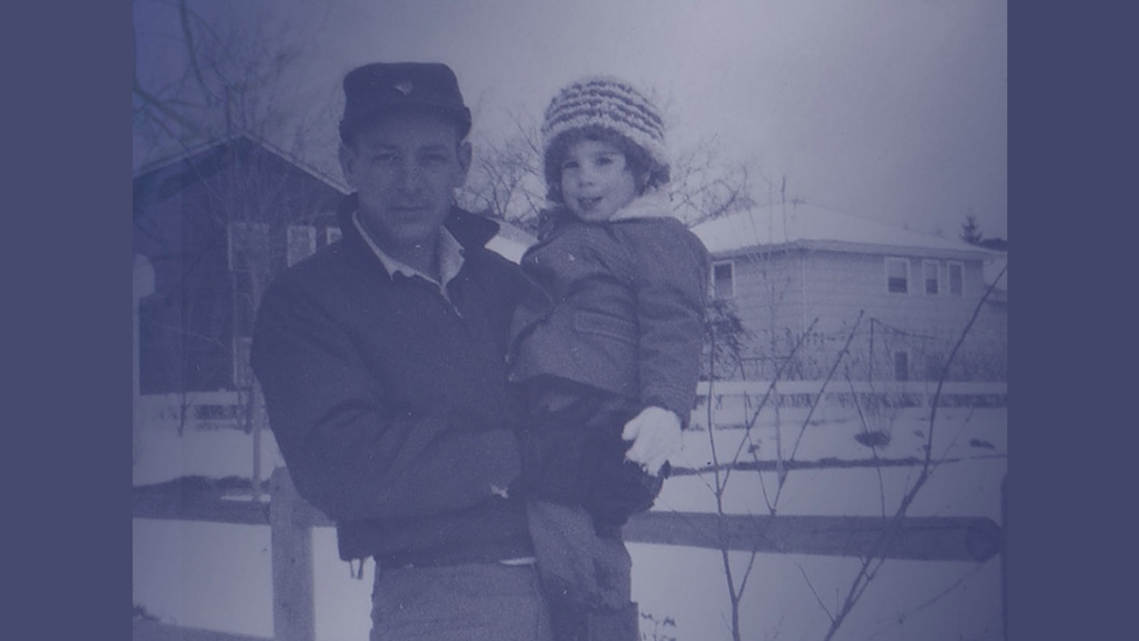 picture of middle aged man holding a young child in the snow with blue filter