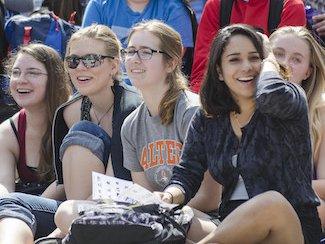 Women watch an outdoor class competition