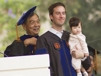 A man holding a baby receives his cowl at graduation