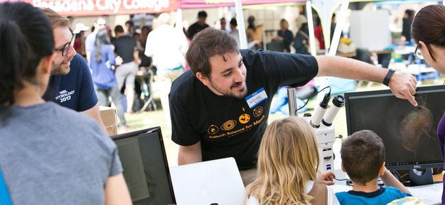 Caltech student showing event visitors a graphic on a computer screen.