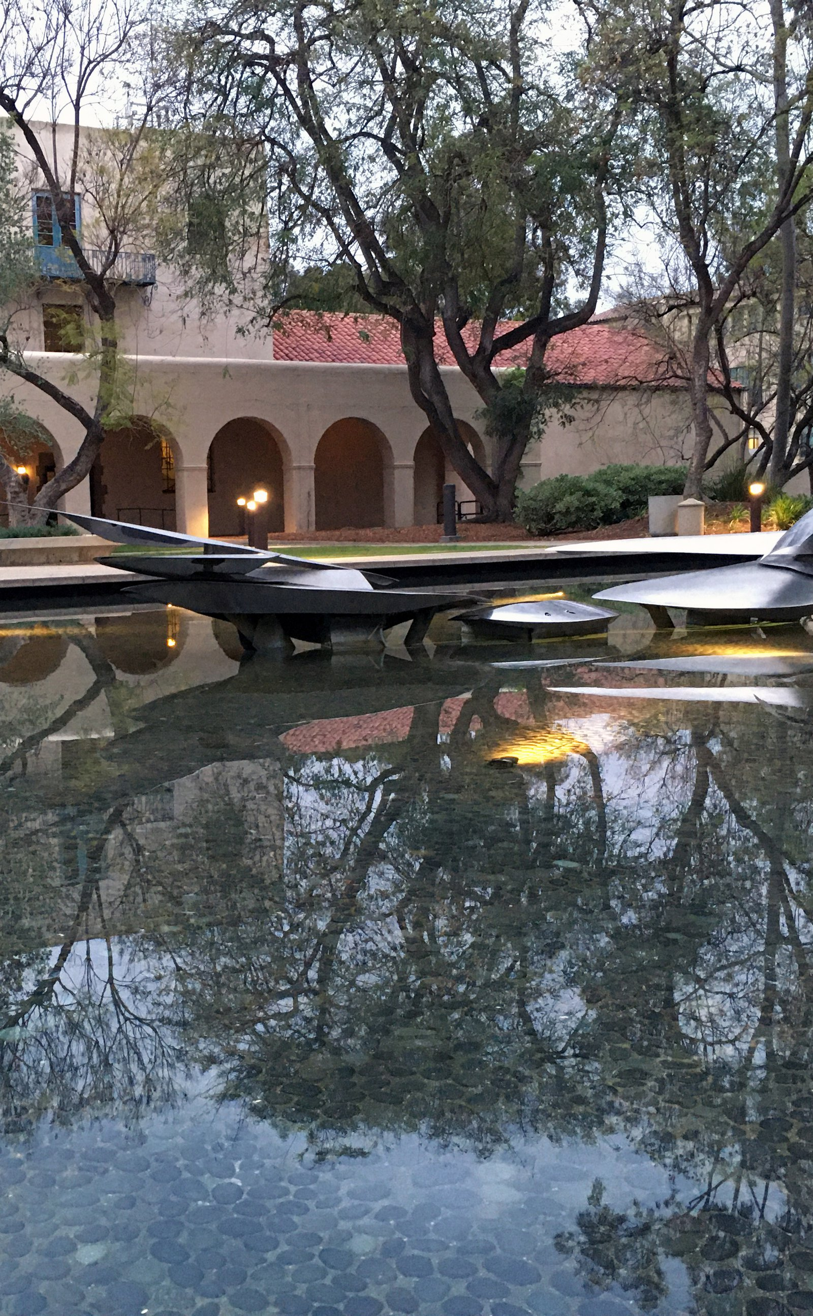 Part of the Water Forms sculpture by George Baker in an ornamental pool on Caltech's campus with trees and Dabney Hall in the background