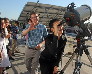photo of students and postdoctoral scholar using a telescope on Caltech rooftop