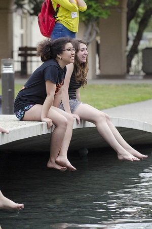 Prospective students sitting on the bridge in front of Millikan Library