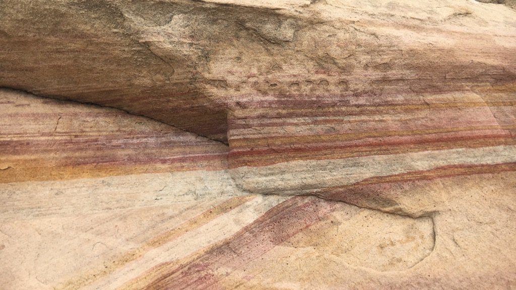 Brown, red, orange, and yellow intersecting stripes in sandstone cross beds.