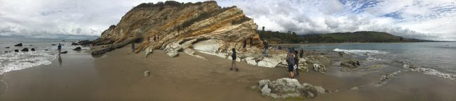 A panorama photo of tilted beds of tan to orangey and whitish rock, with black bands of oily tar, with students scrambling around, adjacent to the ocean.