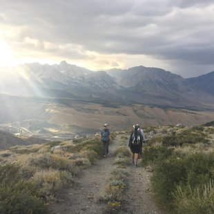 Three people hike down a dirt road, above a valley with sunlit mountains in the far distance, and the sun setting with beams of light from the corner of the photo.