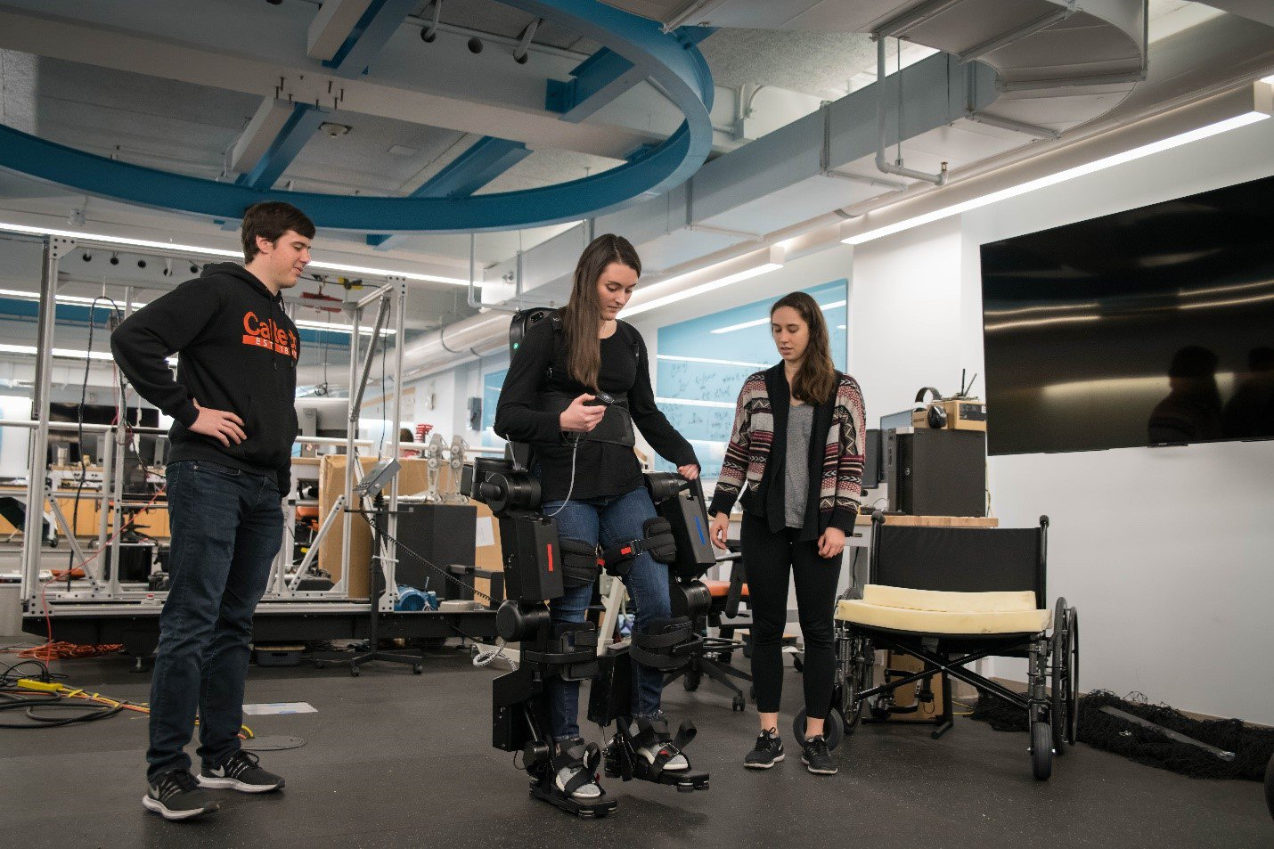 Maegan (center) testing the responsiveness of an exoskeleton.