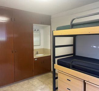 View of a Marks/Braun double, furnished with a bunk bed and built-in closet, cupboards, and sink
