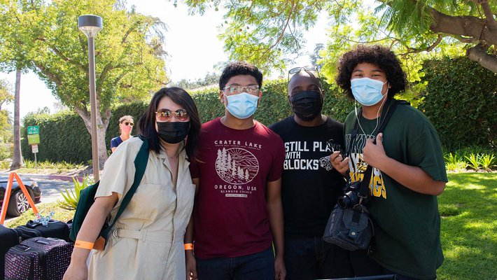 Family poses for the camera during move-in, wearing face masks