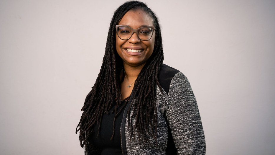 Professional photo of black woman with glasses posing for a portrait