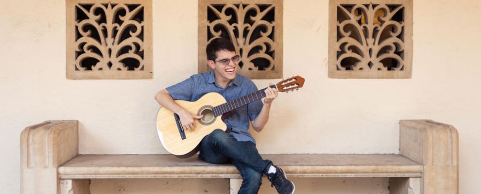 Felipe playing guitar on bench
