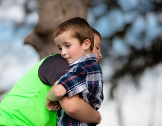 young boy being hugged