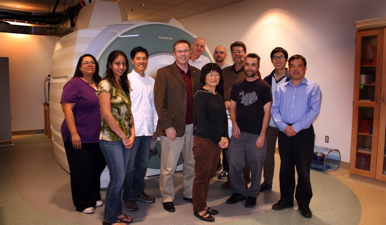 CBIC staff photograph in front of scanner
