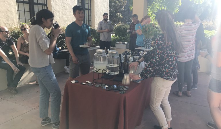 CWiN members, graduate students and postdocs, socializing on an outside patio by a table of food and drinks.