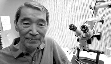 Headshot Mark Konishi sitting next to a microscope.