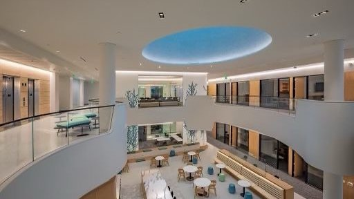 View of the interior of the building from the third floor gallery, it shows the tiles skylight and the second floor write up and social areas.