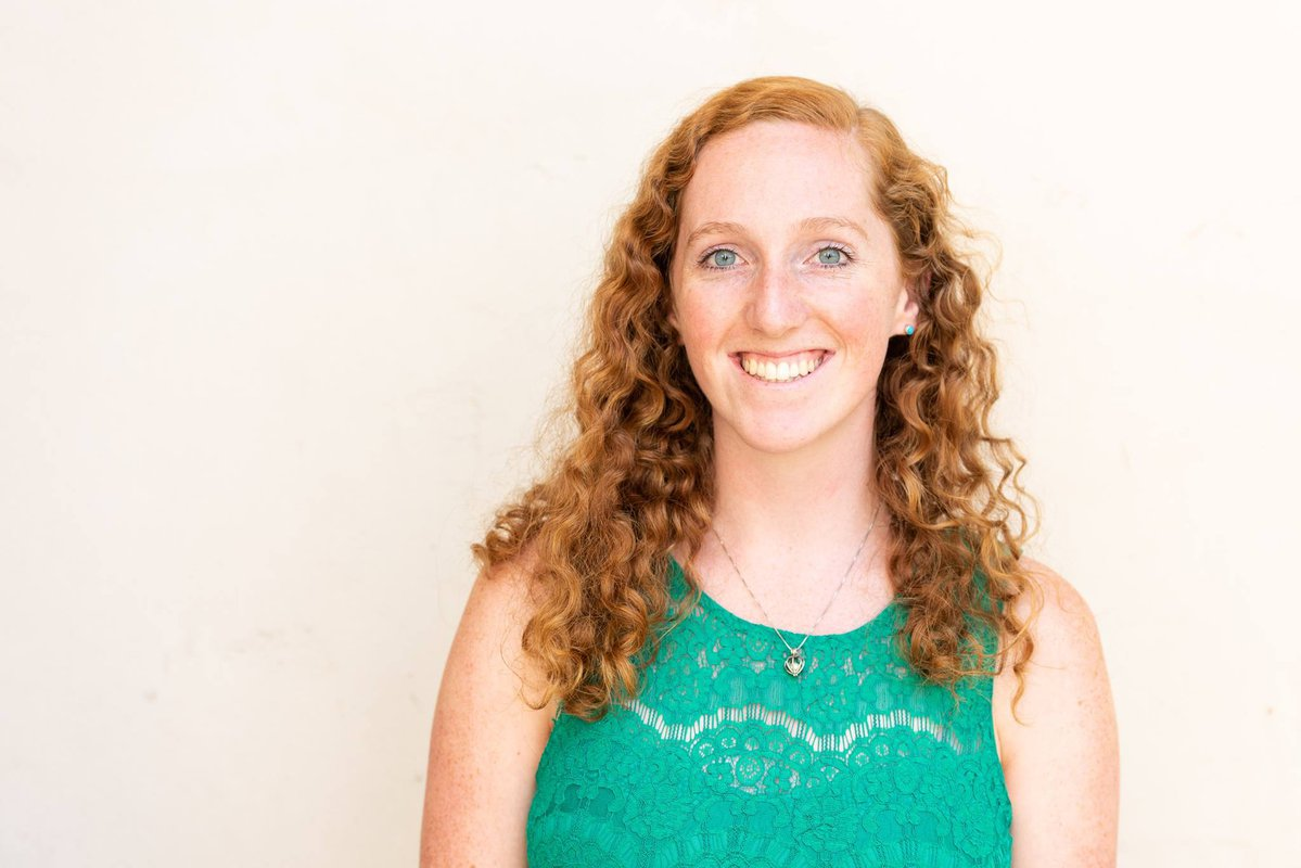 Smiling portrait of graduate student Jackie Dowling in a teal top against a white background