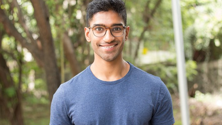 A portrait of Eshaan Patheria. He wears glasses and a T-shirt and smiles at the camera.