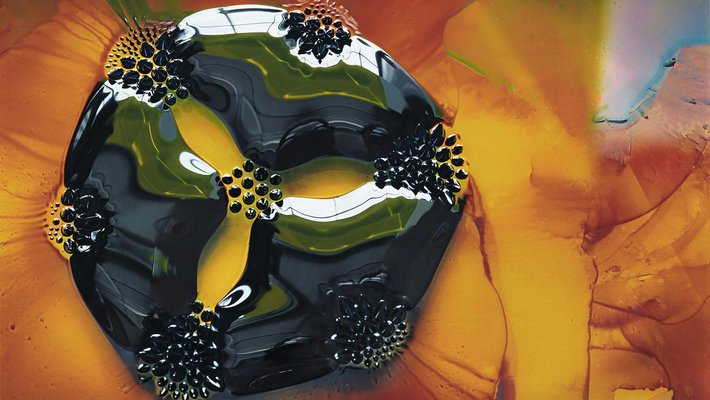 photo of a 2-cm drop of ferrofluid, placed on a glass slide, under which are seven circular magnets.