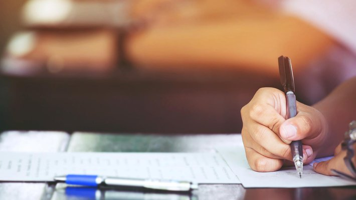 Stock photo of a person's hand writing on a paper at a desk