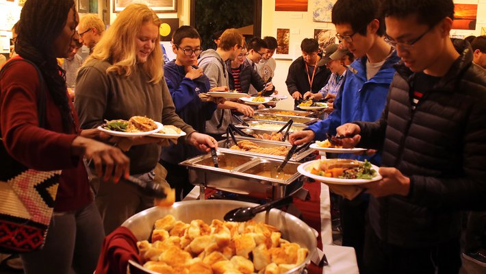 Postdocs and grad students line up to scoop traditional Thanksgiving dishes onto plates