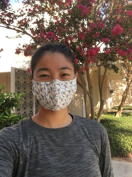 Outdoor selfie of student Renee Wang in a floral face covering