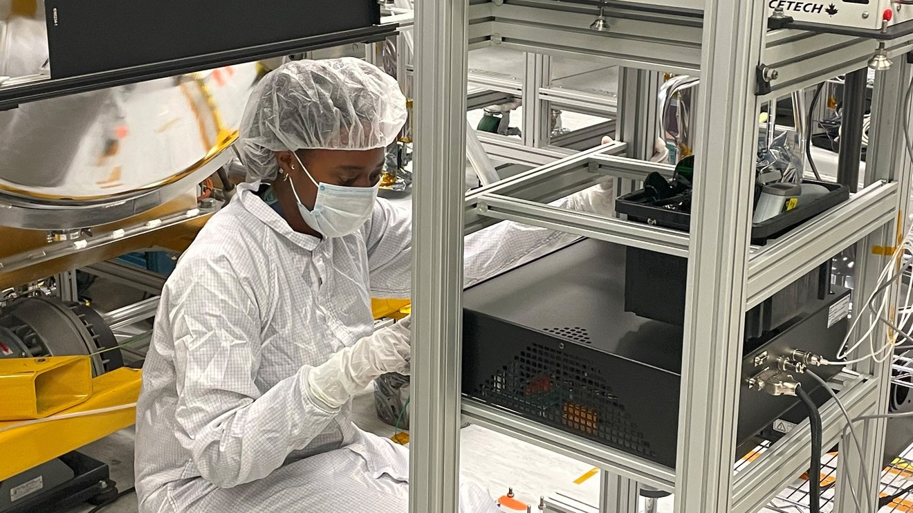 photo of Janelle Wellons working, wearing a clean room suit