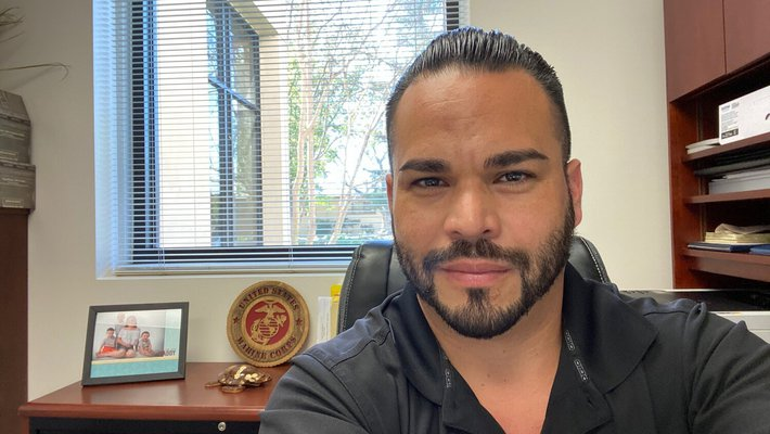 Selfie of Juan Balcazar wearing a Caltech polo in his office with a Marine Corp sign and photo of a family in the background