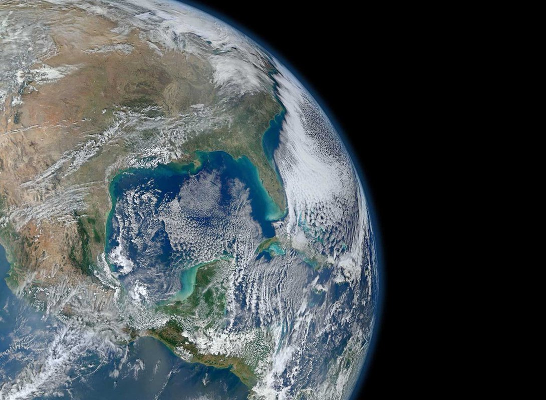 An image of Earth from orbit. Blue ocean and swirling white clouds are seen.
