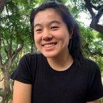 Jiang smiling at the camera, outdoors in a black t-shirt